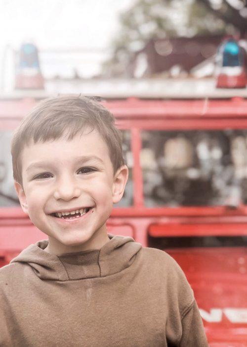 happy-kid-with-a-fire-truck-73U6HZC